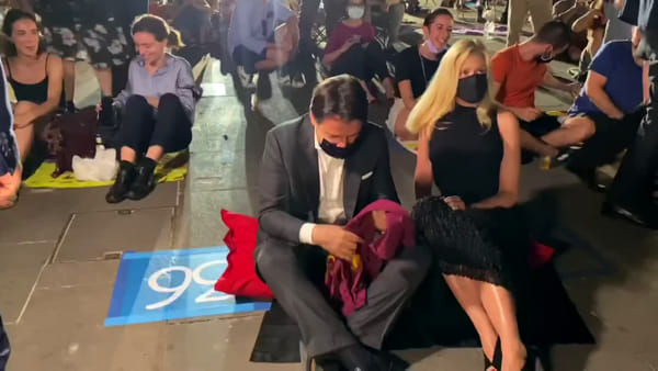 Conte in prima fila seduto per terra con la compagna Olivia Paladino alla prima del Cinema America a Roma