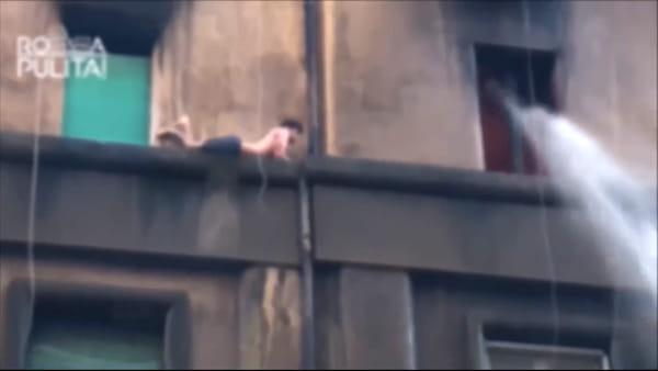 Appartamento in fiamme, il ragazzo per salvarsi scappa sul cornicione: le immagini del salvataggio